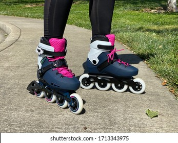 San Jose, CA - April 20, 2020: Closeup of young woman's feet, wearing new roller skates on a sidewalk at the park.