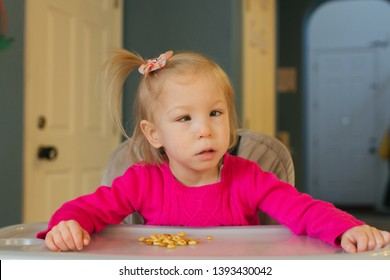 San Jose, CA - April 3, 2019: Autistic toddler girl in pink sweater at home eating Cheerios while sitting in her high chair. Looking at camera, has eye sight difficulties.