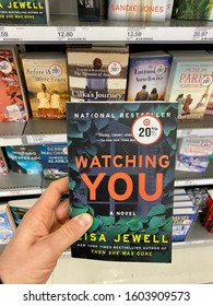 """San Jose, CA - December 28, 2019: Man holding a book titled """"Watching You"""" by Lisa Jewell inside Target store. National Bestseller."""