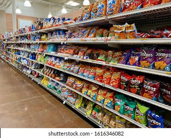 San Jose, CA - January 12, 2020: Isle of snack with rows of shelves filled with different chips and pop corn bags inside a supermarket.