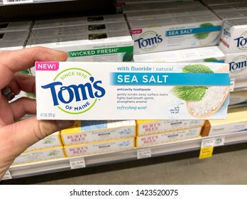 San Jose, CA - June 11, 2019: Man holding a box of Tom's of Maine sea salt toothpaste with fluoride inside Whole Foods.