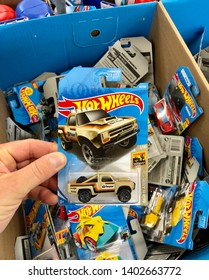 San Jose, CA - May 19, 2019: Large box of HotWheels cars on sale, man holding one up above the others.