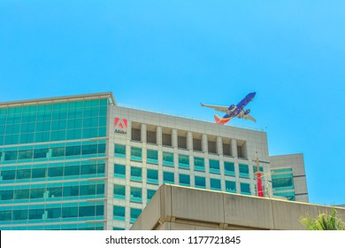 San Jose, CA, United States - August 12, 2018: Adobe headquarters skyscraper in Silicon Valley, with an airplane flying above from the close international airport Norman Y. Mineta of San Jose.