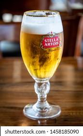 San Jose, CA/USA 07/20/2019 Glass containing Stella Artois brand pilsen style draft beer over a bar counter