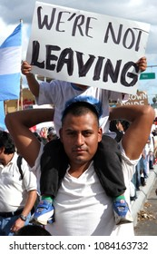 "San Jose, CA/USA - April 10, 2006: Mexican Americans march in support of equal rights for immigrants during a rally in San Jose, California. A man holds a sign that says ""We're not leaving""."