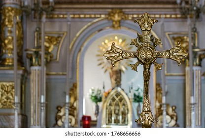 San Jose Caves, Spain, March 21, 2019 Crucifix on the altar inside a church. Big golden crucifix used for masses placed on the altar of the church with the background out of focus.