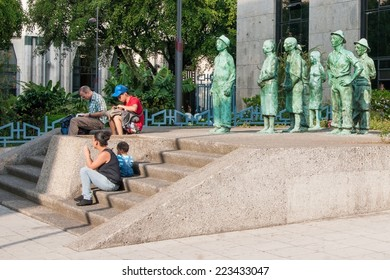 SAN JOSE, COSTA RICA - JANUARY 16, 2013: Everyday people sitting in front of everyday 'Tico' sculptures in San Jose, Costa Rica on Jan. 16, 2013 in San Jose, Costa Rica (Central America)