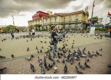San Jose / Costa Rica - September 24, 2015: Locals feed pigeons in front of the national theatre at the central Juan Mora Fernandez city plaza.