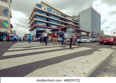 San Jose / Costa Rica - September 24, 2015: Pedestrians cross the street at the capital's downtown area in front of the national treasury building.