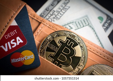 San Jose, United States - March 27, 2018: Bitcoin. Gold coin with bitcoin symbol cash and credit / debit cards Visa and MasterCard in a wallet