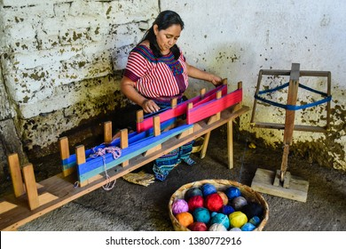 San Juan la Laguna, Guatemala- October 14, 2017: A Guatemalan local woman demonstrates cotton hand weaving process. The many colors of the thread are provides by vegetable dyes from different plants.