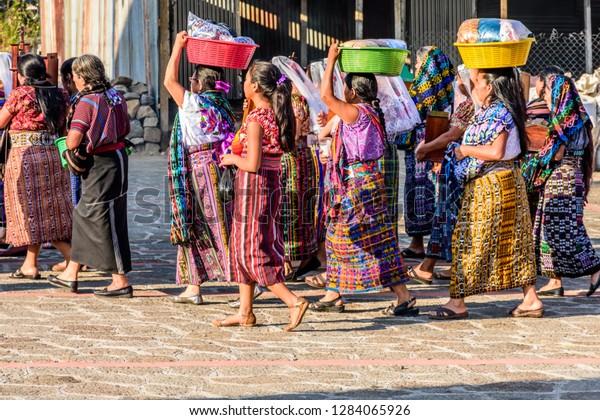 San Juan la Laguna, Lake Atitlan, Guatemala - December 31, 2018: Procession of Tz'utujil Maya women in traditional clothing head to church on New Year's Eve in lakeside village of San Juan la Laguna