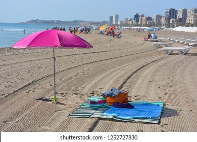 San Juan Playa, Alicante, Alicante Province, Comunidad Valencia, Spain. September 3rd 2015. Bright and colorful beach umbrella and towels on the sand, looking towards Alicante city skyline.