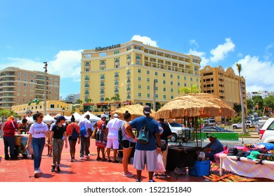 San Juan, Puerto Rico - August 20th 2019: Tourists from the docked cruise ships browse the souvenir stalls along the promenade just outside the cruise port terminal of San Juan.