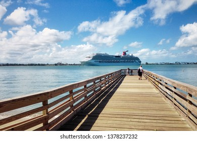 San Juan / Puerto Rico - Jan 18, 2017:  Long wooden dock leading to the sea with carnival cruise ship passing by. Travel picture.