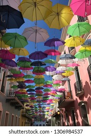 San Juan, Puerto Rico, US Territory- November 21 2018 - street lined with colorful umbrellas hanging above with  blue and pink buildings on each side
