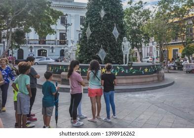 San Juan, Puerto Rico, USA - Jan. 2, 2018: People watching street performer disguised as marble statue in Plaza de Armas (Armas Square) in Old San Juan