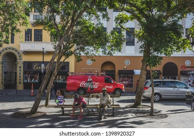San Juan, Puerto Rico, USA - Jan. 2, 2018: Father and daughter resting on a bench with statue in Plaza de Armas (Armas Square) in a sunny afternoon in Old San Juan