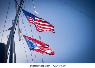 San Juan, Puerto Rico, USA - November 26 2014: The flags of United States and Puerto Rico waving on a boat in San Juan.