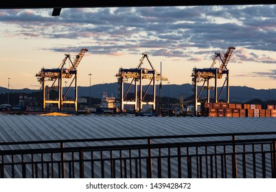 SAN JUAN, PUERTO RICO/U.S.A. - January 29, 2019: Photo of three dockyard cranes at dusk in the port near one of the cruise ship terminals.
