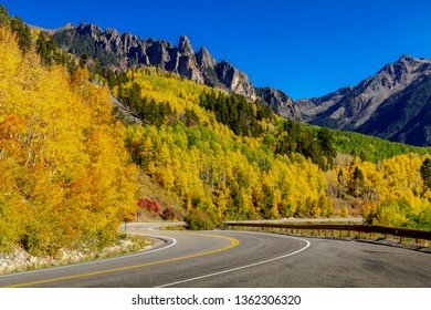 San Juan Sky Way scenic byway surrounded by changing yellow aspen trees on sunny autumn afternoon