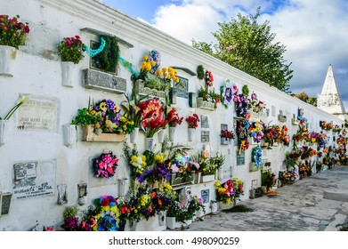San Lazaro Cemetery, Antigua, Guatemala - November 2, 2014:  Flowers & wreaths cover mausoleum on All Souls' Day in Spanish colonial town of Antigua.