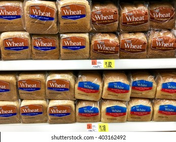 San Leandro, CA - April 08, 2016: Great Value wheat bread, wheat bread with honey and white bread on a grocery store display. Generic brand with lower price than the competition
