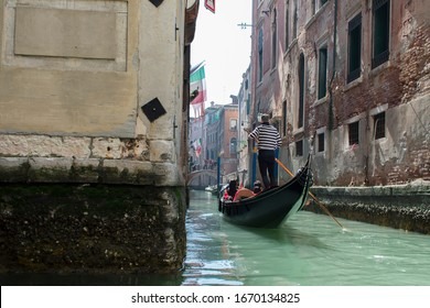 San Marco / Venice / Italy - April 17, 2019: Tourists in gondola ride in the historic city of Venice in Italy. Small canal