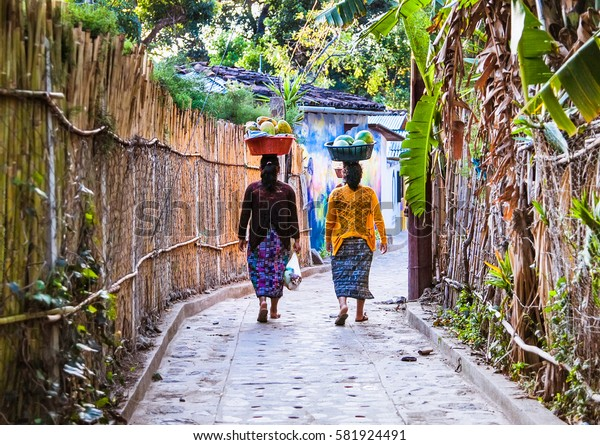 SAN MARCOS, GUATEMALA-DEC 24, 2015: Two women carry on their heads baskets with watermelons on Dec 24, 2015 in San Marcos, Guatemala.