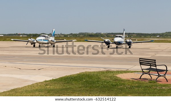 SAN MARCOS, TEXAS - APRIL 26 2017 two twin engine planes parked and a metal bench