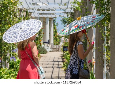 San Marino, CA / USA - June 10, 2016: Ladies with parasols at Huntington Library on a warm June day