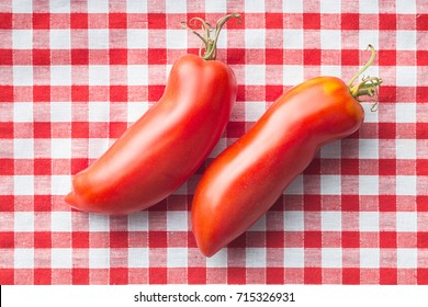 San marzano tomatoes on checkered tablecloth.