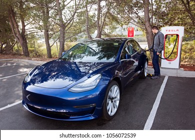 San Mateo, CA - January 1, 2018: young man charging newest navy tesla model 3 at supercharger station
