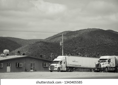 San Luís Potosí, Mexico - February 16, 2017: White camions park by the highway, next to a building. Behind them mountains.