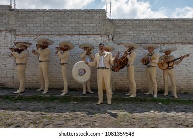 San Miguel de Allende, Gaunajuato / Mexico - October 01 2016: Mariachi group performs on street in front of brick wall