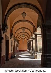 """San Miguel de Allende, Guanajuato / Mexico - 02 22 2016: One point perspective view of one of the corridors of ex-convent Centro Cultural """"El Nigromante"""" in San Miguel de Allende"""