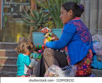San Miguel de Allende, Guanajuato / Mexico - 02 22 2016: Native Mexican woman and child selling dolls in the streets of San Miguel de Allende