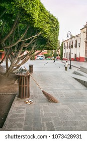 San Miguel de Allende, Mexico -  July 14, 2015.  An old straw broom resting against a rubbish bin in San Miguel.  A typical street scene in San Miguel de Allende.
