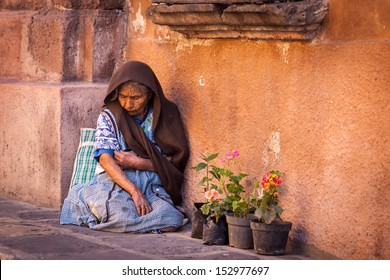 SAN MIGUEL DE ALLENDE, MEXICO - JANUARY 6. An unidentified senior woman in poverty sells flowers on the street of San Miguel de Allende, Mexico on January 6, 2013.