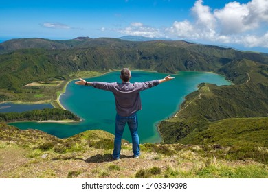 San Miguel, Portugal - May 13, 2019: Adult man stands on the background of a lake and mountains. The concept of healthy leisure and travel.