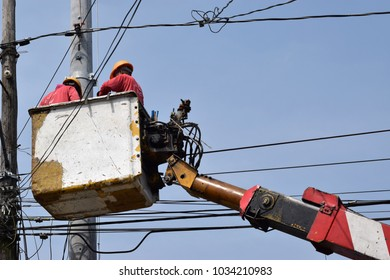 San Pablo City, Laguna, Philippines - February 26, 2018: Electrical Workers On Telehandler With Bucket installing High tension wires. Underside view low angle