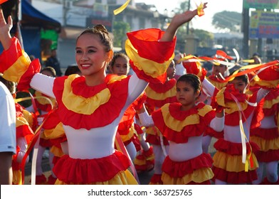 SAN PABLO CITY, LAGUNA, PHILIPPINES - JANUARY 17, 2016:  School girls parade and dance on the street in colorful costumes, carrying Infant Jesus icon to celebrate the annual sinulog festival