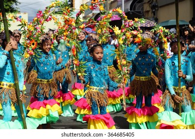 SAN PABLO CITY, LAGUNA, PHILIPPINES - JANUARY 13, 2016: a group of carnival dancers in various costumes frenzy dance along the road during the 21st annual coconut festival cultural celebration.