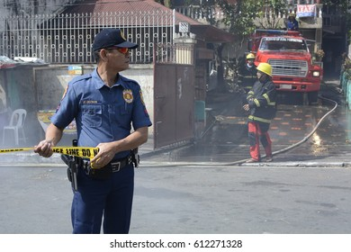 SAN PABLO CITY, LAGUNA, PHILIPPINES - MARCH 7, 2017: Police officer help maintain order during house fire that gutted interior shanty houses