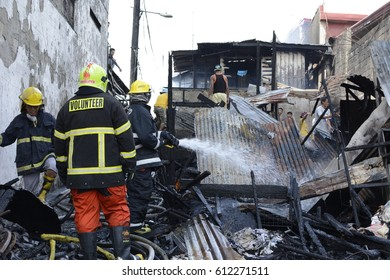 SAN PABLO CITY, LAGUNA, PHILIPPINES - MARCH 7, 2017: Local fireman help extinguish fire during house fire that gutted interior shanty houses