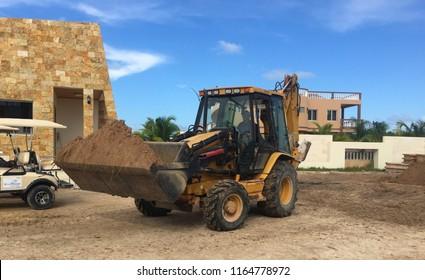 San Pedro, Belize - August 24, 2018: Construction worker drives a Cat Backhoe on La Sirene construction site.
