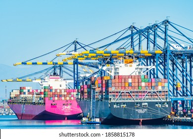 San Pedro, California - October 11 2019: Express Rome and One Olympus Cargo Ships container loaded and docked at Port of Los Angeles in San Pedro, California, below cranes at the wharf/ pier/ berth.