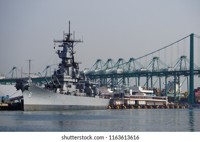 San Pedro, California USA - August 9, 2018: Battleship Iowa in the Port of Los Angeles against a backdrop of gantry cranes and equipment, the Vincent Thomas suspension bridge in background.