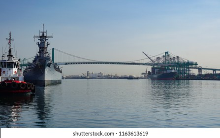 San Pedro, California USA - August 9, 2018: Port of Los Angeles main channel with tugboat, Battleship Iowa, Vincent Thomas bridge and a container ship at its berth being loaded by gantry cranes