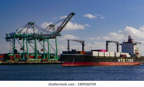 San Pedro, California USA - February 5, 2019: Loaded container ship NYK Maria in main channel of Port of Los Angeles approaching  docks and gantry cranes.